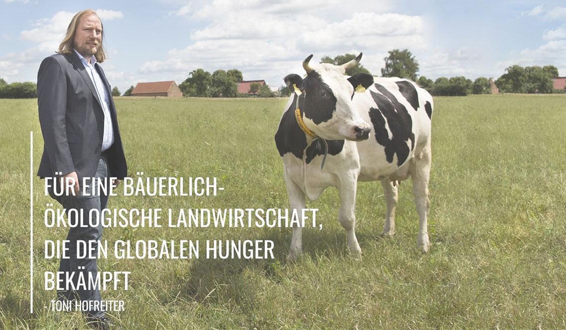 """Toni steht neben einer Kuh. Auf dem Bild steht: """"Für eine bäuerlich-ökologische Landwirtschaft, die den globalen Hunger bekämpft."""" Im Hintergrund stehen Bäume und es ist eine Wiese zu sehen."""