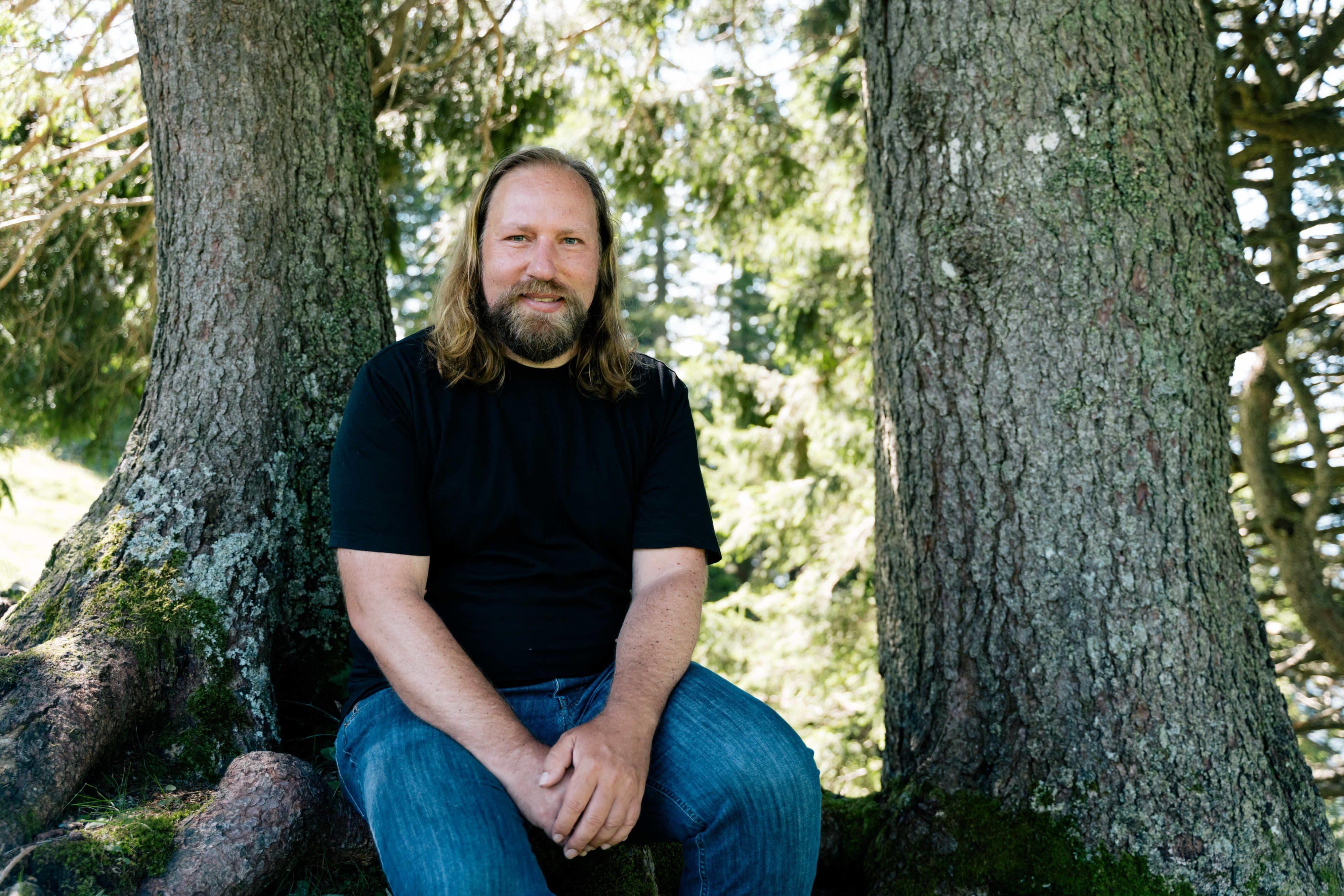 Anton Hofreiter sitzend vor zwei Bäumen in der Natur