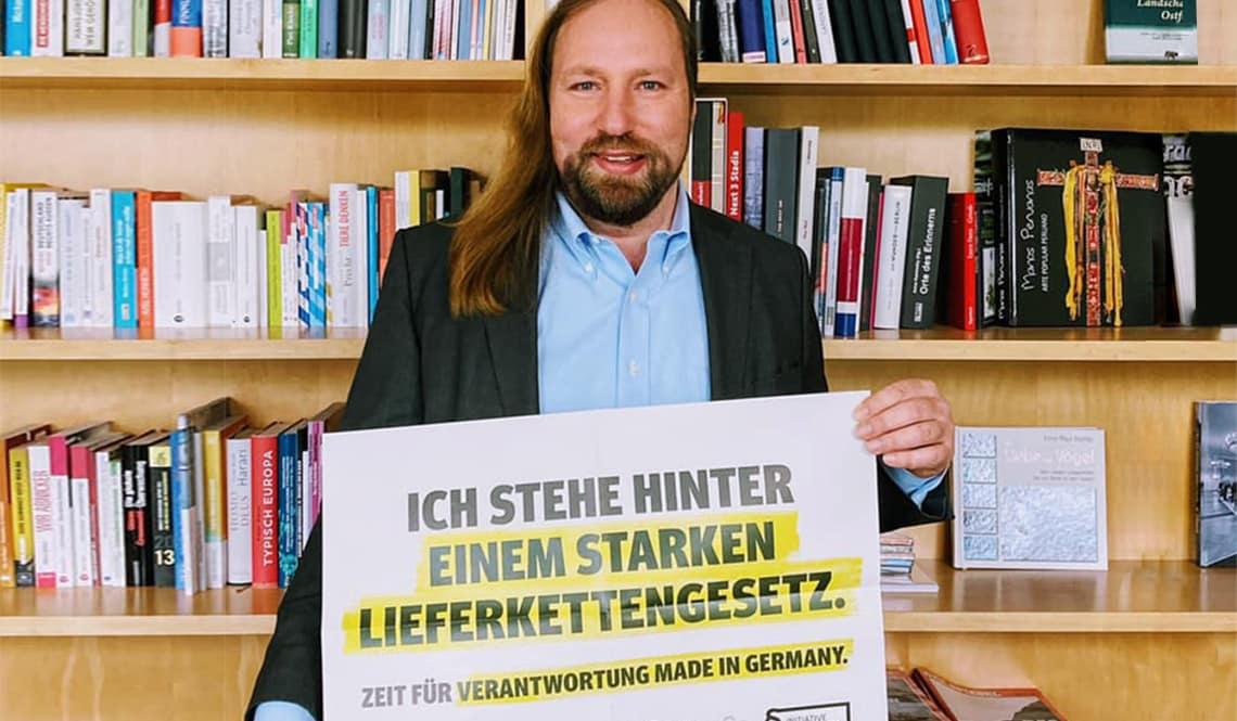 """Toni Hofreiter steht vor einem Bücherregal. Er hält ein Schild in der Hand auf dem Schild steht: """"Ich stehe hinter einem starken Lieferkettengesetz""""."""