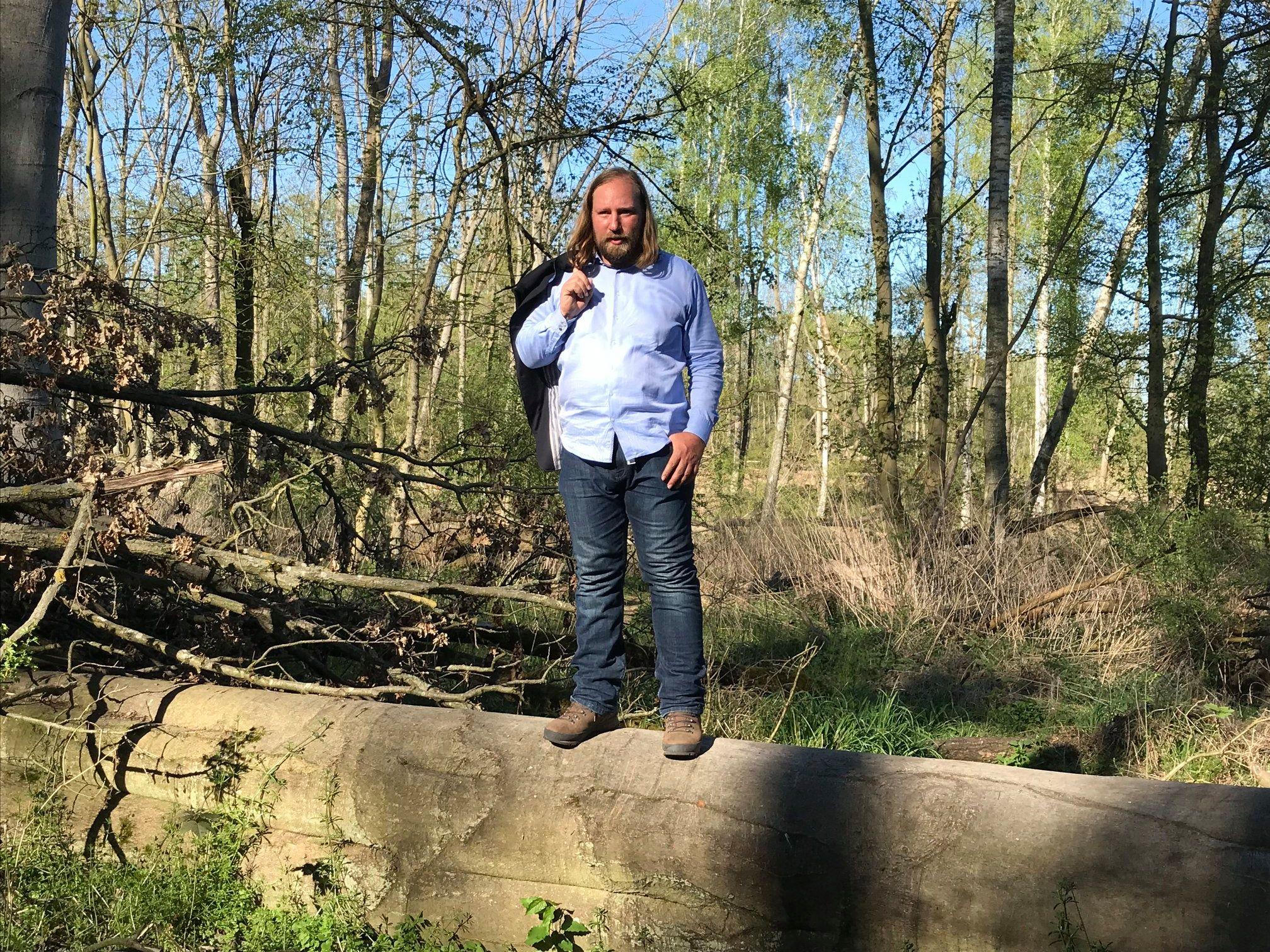 Toni steht auf einem Baumstamm. Er hat die Jacke über seine Schulter geworfen und schaut in die Kamera. Im Hintergrund ist Wald zu sehen.