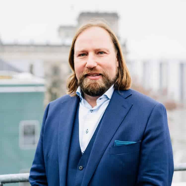 Toni steht im blauen Anzug auf der Terrasse der Reichstagskuppel. Er lächelt.