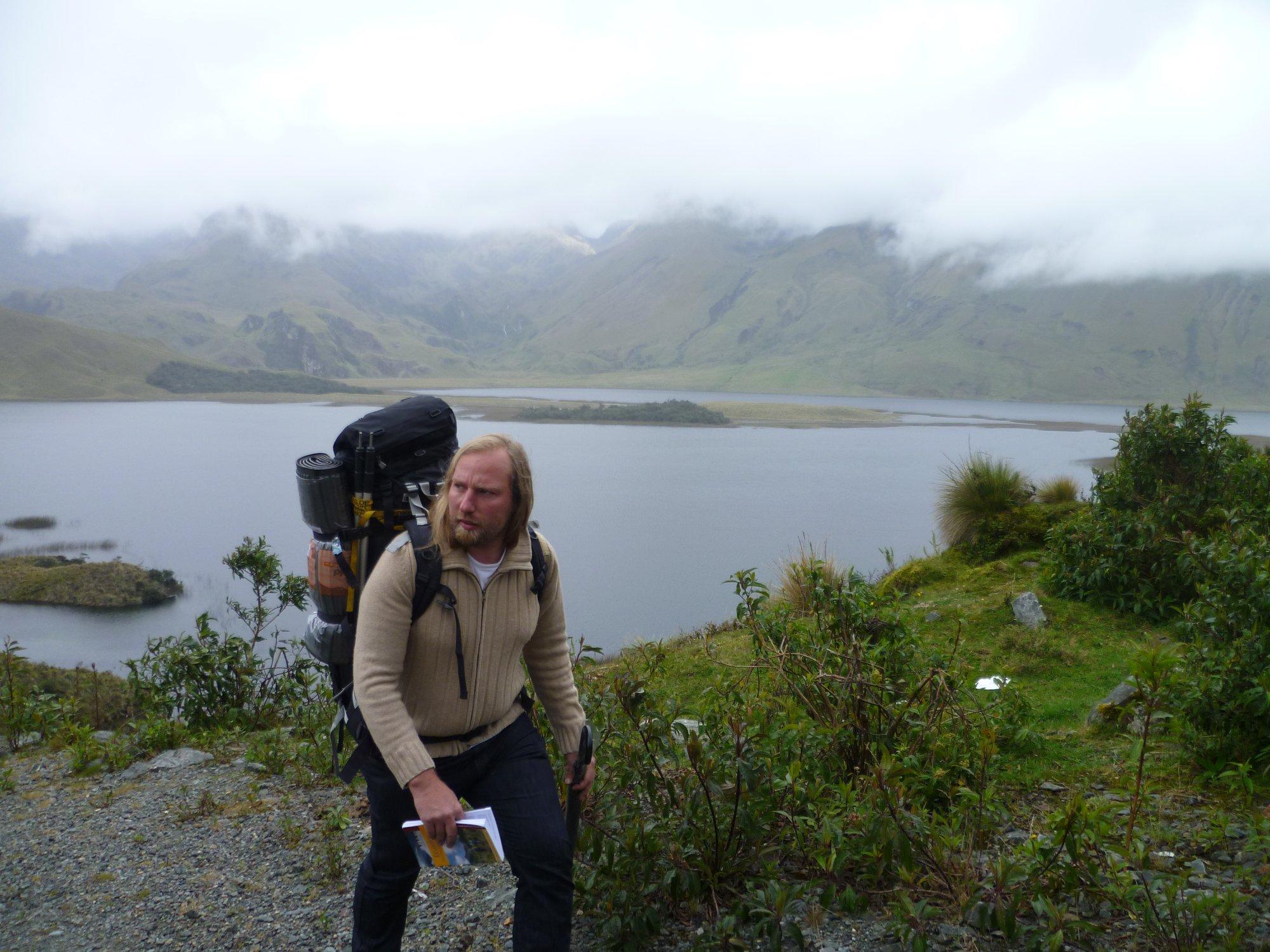 Auf dem Foto sieht man Toni mit einem Wanderrucksack und einem Reiseführer. Er wandert an einem See entlang. Der See ist im Hintergrund zu sehen.