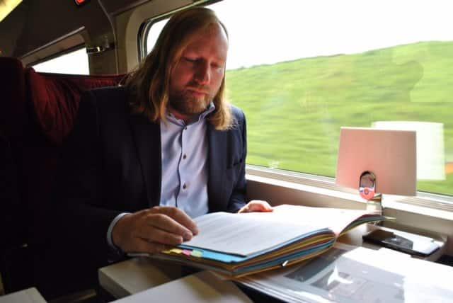Toni sitzt im Zug und liest. Da das Bild vor der Pandemie entstanden ist, trägt er keinen Mund-Nasen-Schutz.