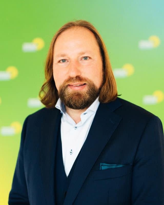 Anton Hofreiter Portrait mit grünem Hintergrund im Anzug