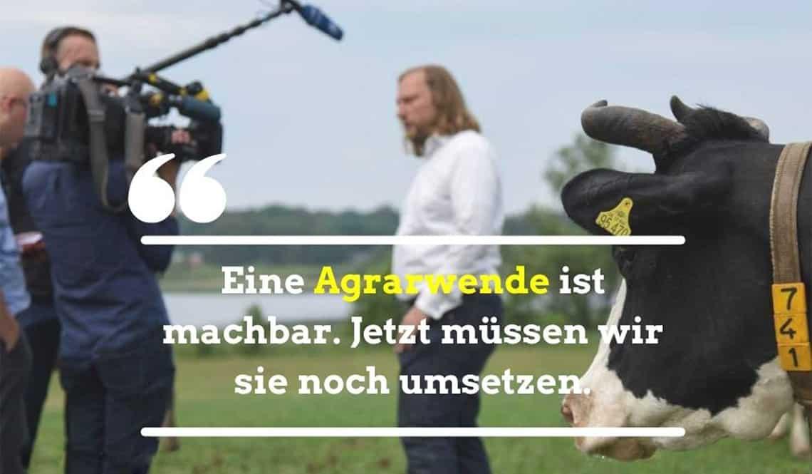 """Toni steht im Hintergrund. Es ist eine Kuh zu sehen. Auf dem Bild steht der Text: """"Eine Agrarwende ist machbar. Jetzt müssen wir sie noch umsetzen."""""""