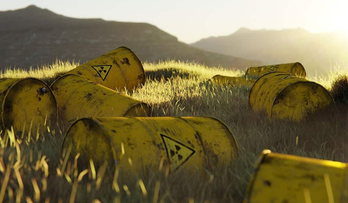 Gelbe Tonnen, auf denen der Warnhinweis vor Atommüll angebracht ist. Sie liegen in der freien Natur auf Gras.