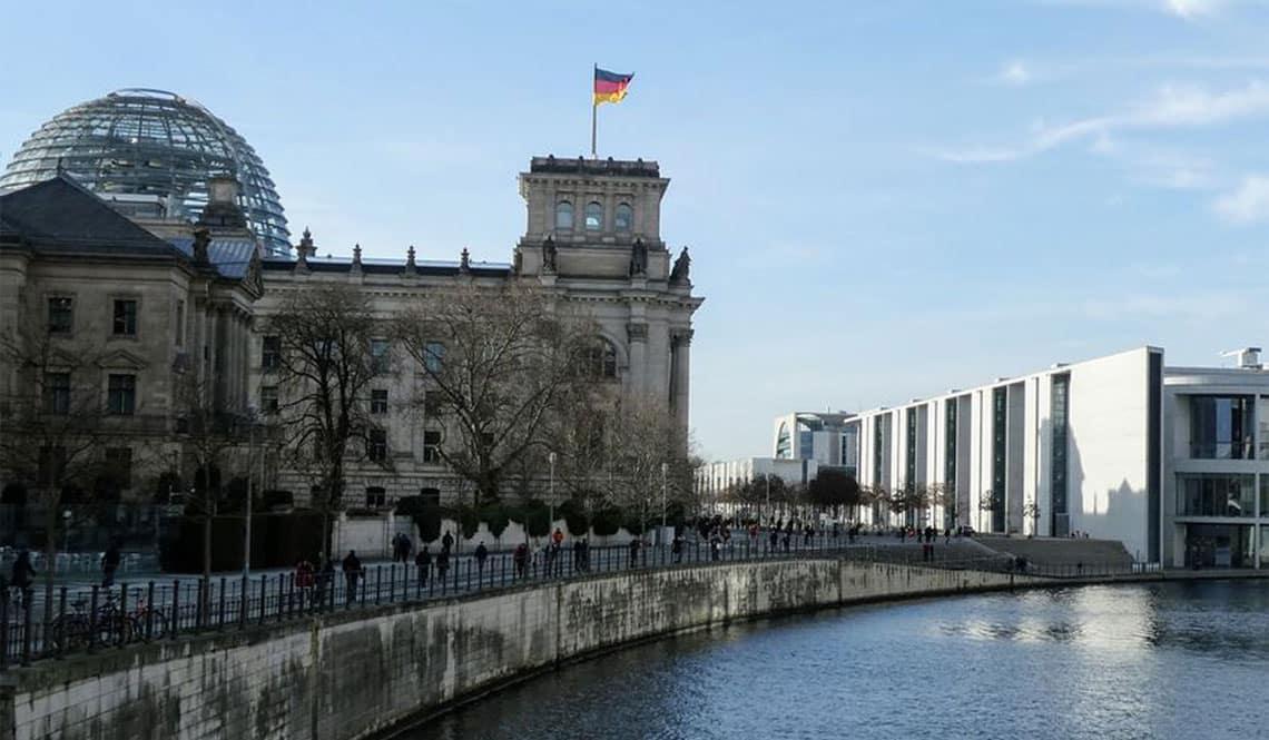 Der Sitz des Bundestagses mit der Kuppel steht links der Spree. Es sind Teile des Elisabeth-Lüders-Hauses zu sehen. Der Himmel ist blau.