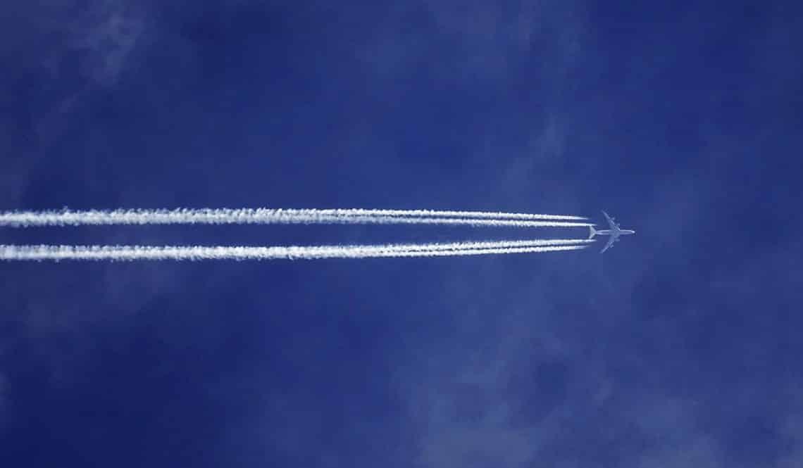 Auf dem Bild sind man ein Flugzeug am Himmel mit zwei Kondensstreifen. Der Himmel ist blau.
