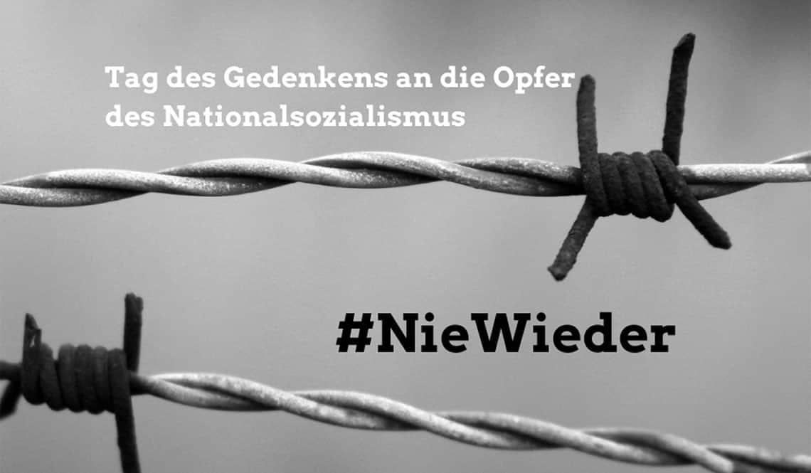 """Maschendrahtzaun in schwarz-weiß. Auf dem Bild steht """"Tag des Gedenkens an die Opfer des Nationalsozialismus"""". Außerdem: """"#NieWieder""""."""