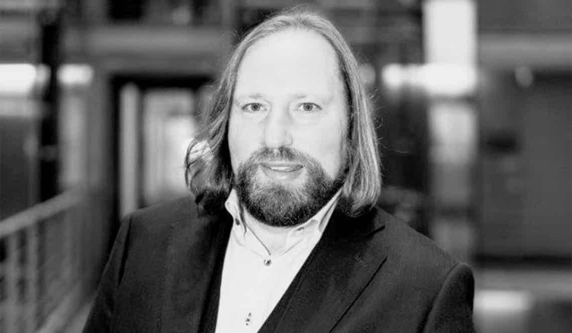Auf dem Bild ist Toni Hofreiter zu sehen. Er trägt einen Anzug und lächelt in die Kamera. Das Foto ist schwarz-weiß.