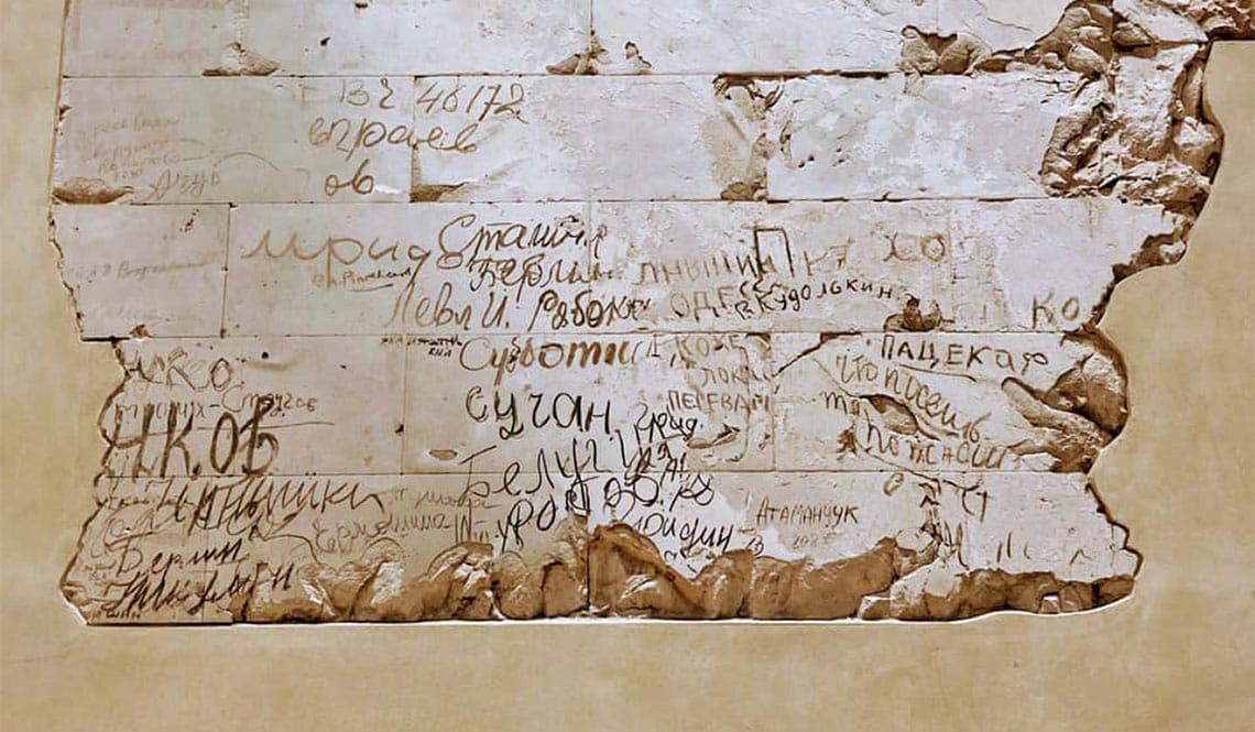 Graffitis und Einschusslöcher der sowjetischen Soldaten auf einer Mauer im Inneren des Sitzes des Bundestags.